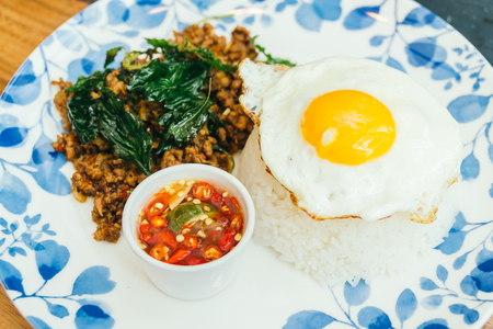 Spicy pork with basil leaf and rice on top with fried eggs in plate - Thai food style