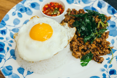 carne picada: Spicy pork with basil leaf and rice on top with fried eggs in plate - Thai food style