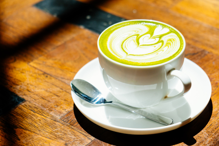 Green tea matcha latte in white cup on table - Vintage Filter