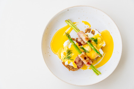 benedict: Eggs benedict with bacon twist asparagus in white plate Stock Photo
