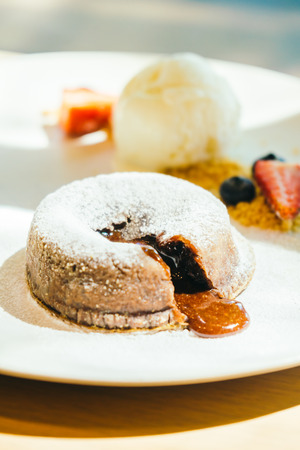 Sweet dessert with Chocolate brownies lava cake with ice cream and fruit in white plate