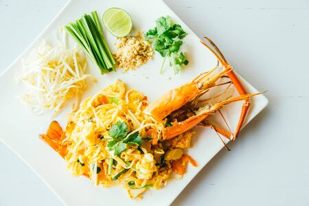 Pad thai noodles with jumbo prawn and vegetable in white plate
