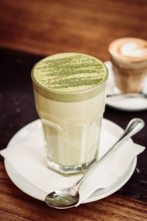 Hot matcha green tea latte cup on table in cafe shop - Vintage Filter Stock Photo