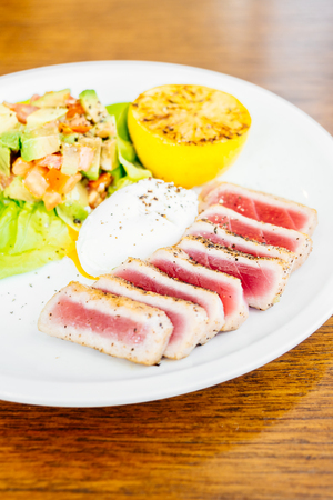 Grilled Tuna tartare with avocado and tomato in white plate
