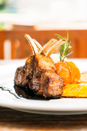Grilled lamb chop steak with vegetable and sauce in white plate
