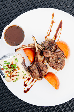 Grilled lamb chop with sauce in white plate