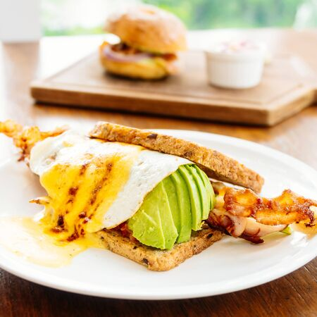 Sandwich with avocado bacon and asparagus in white plate Lizenzfreie Bilder
