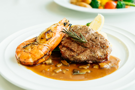 Surf and turf or Grilled beef meat with prawn steak and vegetable in white plate