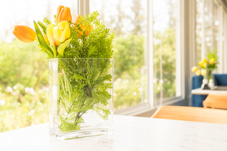 Interior room: Plastic or fake flower in vase on table for decoration