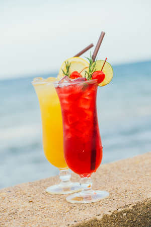 Iced juice cocktails drinking glass with beach and sea background