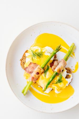 Eggs benedict with bacon twist asparagus in white plate Lizenzfreie Bilder