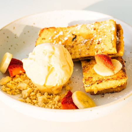 Sweet dessert french toast and ice cream with banana and strawberry in white plate