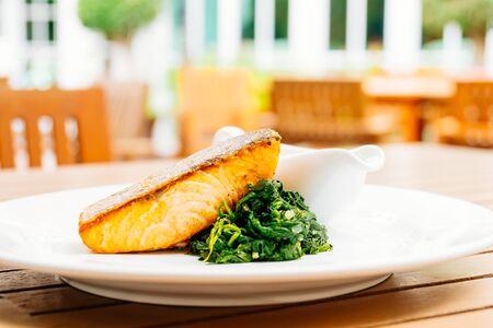 Grilled salmon steak with vegetable and sauce in white plate Lizenzfreie Bilder