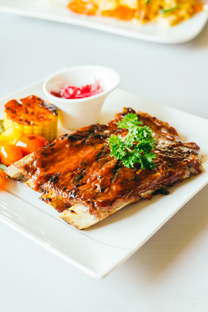 Grilled pork ribs with bbq sauce in white plate