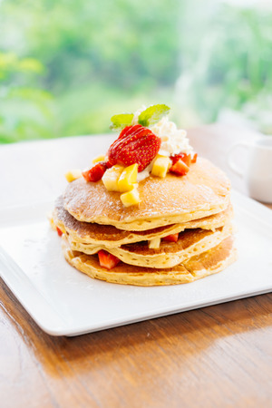 Sweet dessert stack of pancake with strawberry on top in white plate