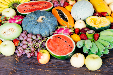 Assorted and mixed fruits on wooden background with copy space - Healthy food concept