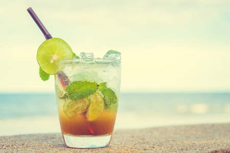 Ice drinking cocktails mojito glass with sea and ocean background - Vintage Filter