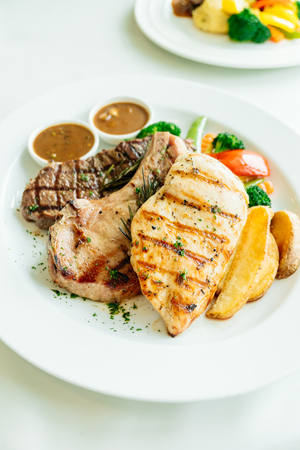 Grilled Chicken breast and Pork chop with beef meat steak and vegetable in white plate Lizenzfreie Bilder