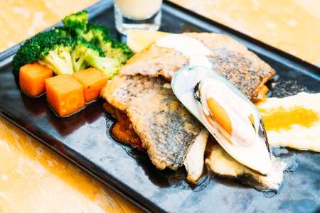 Sea bass and mussel steak in black plate