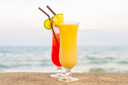 Iced cocktails drinking glass with sea and beach background