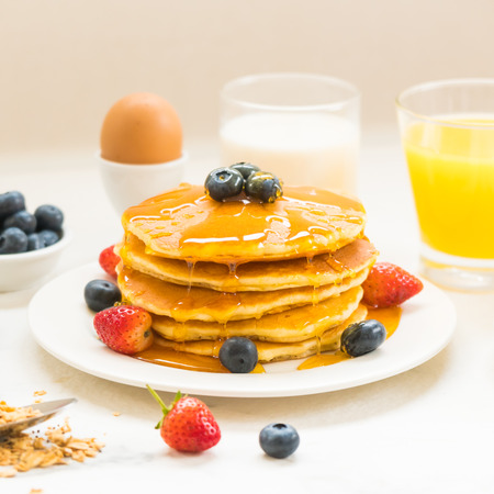 Healthy Breakfast set with Pancake and Granola with blueberry and strawberry and black coffee , Milk and Orange juice on white stone table background Stock Photo