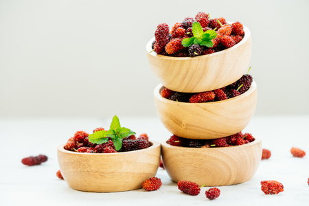 Red and Black mulberry fruit in bowl on white stone background