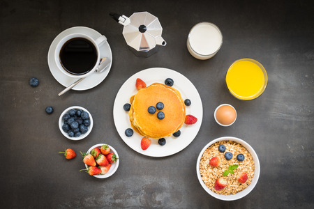 Healthy Breakfast set with Pancake and Granola with blueberry and strawberry and black coffee , Milk and Orange juice on table