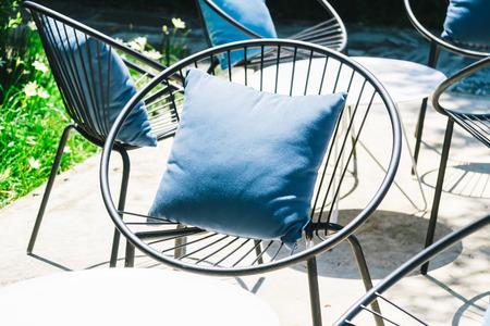 옥외 정원에서 의자 및 테이블 세트에 베개를 가진 안뜰