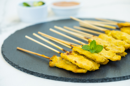 Chicken satay on black slate with sauce