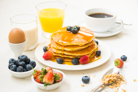 Healthy Breakfast set with Pancake and Granola with blueberry and strawberry and black coffee , Milk and Orange juice on white stone table background Foto de archivo