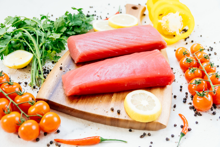 Raw tuna fish fillet meat on wooden cutting board with vegetable and ingredient for cooking 版權商用圖片