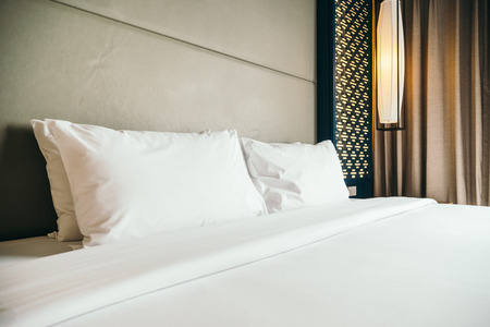 White comfortable pillow on bed decoration in hotel bedroom interior
