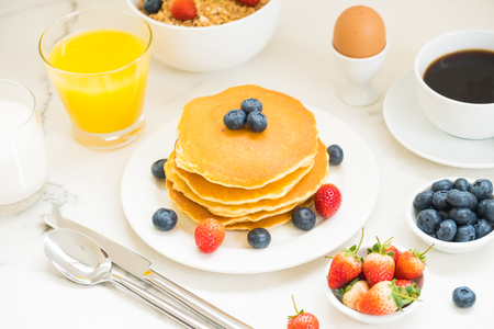 Healthy Breakfast set with Pancake and Granola with blueberry and strawberry and black coffee , Milk and Orange juice on white stone table background Standard-Bild