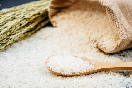 Raw Jasmine rice in wooden bowl  and spoon with grain and seed Standard-Bild