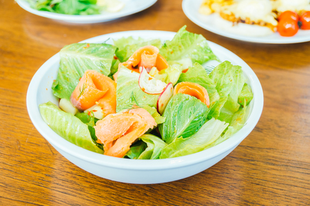 Smoked salmon with vegetable salad in white bowl - Healthy food style Standard-Bild