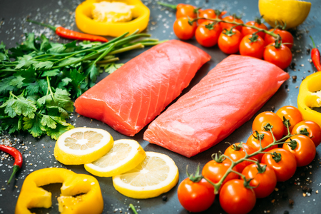 Raw tuna fish fillet meat on wooden cutting board with vegetable and ingredient for cooking on black stone background