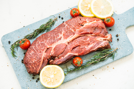 Raw beef meat on cutting board with vegetable and ingredient for cooking