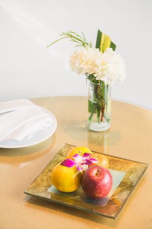Welcome fruit in hotel bedroom with white flower in vase