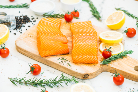 Raw and fresh salmon meat fillet on wooden cutting board with lemon tomato and other ingredient - Healthy food style