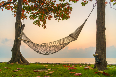 Hammock on the beach and sea on sunrise time - Vacation concept