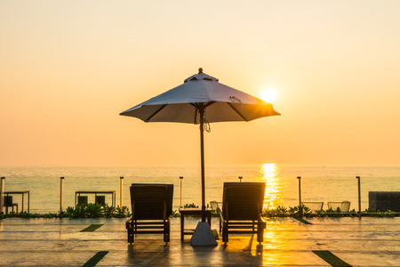 Beautiful umbrella and chair around swimming pool in hotel and resort in sunrise time 免版税图像