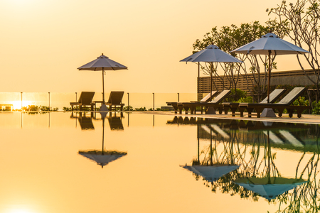 Beautiful umbrella and chair around swimming pool in hotel and resort in sunrise time Stock Photo