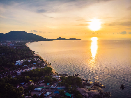 Aerial view of beautiful tropical beach and sea with palm and other tree in koh samui island Thailand at sunrise time for vacation and travel
