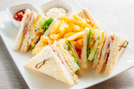 Club sandwich with bacon cheese and ham vegetable and sauce in white plate