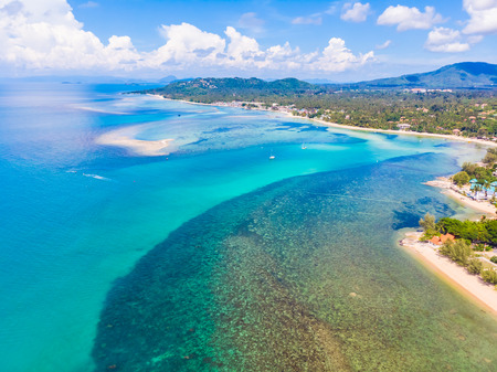 Beautiful aerial view of beach and sea with many tree and white cloud on blue sky in koh samui island for vacation and travel