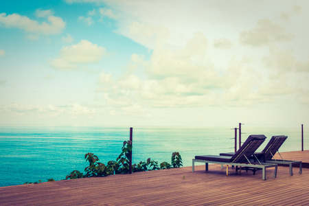 Beautiful tropical sea ocean and blue sky background with bed on patio balcony for travel and vacation