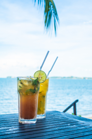 Ice mojito drinking glass with tropical sea ocean and beach view 스톡 콘텐츠