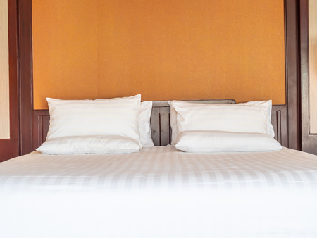 Comfortable pillow on bed with light lamp decoration in hotel bedroom Banque d'images