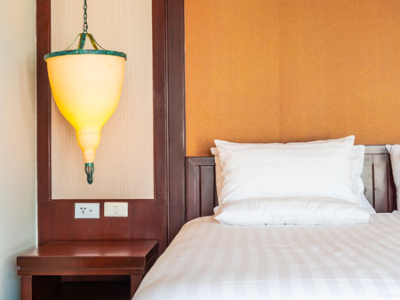 Comfortable pillow on bed with light lamp decoration in hotel bedroom Stock Photo