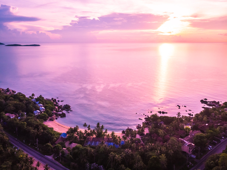 Aerial view of beautiful tropical beach and sea with palm and other tree in koh samui island Thailand at sunset time for vacation and travel